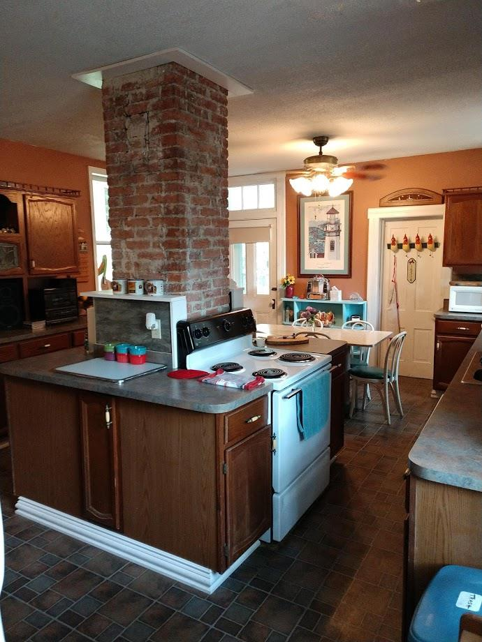 Large eat-in kitchen with exposed brick chimney